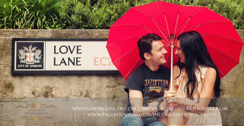 couple sitting on the pavement with red heart shaped umbrella next to the Love Lane EC2 street sign.London engagement photography by gavin conlan photography Ltd
