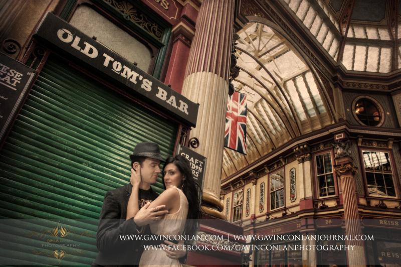 fashion portrait of the couple posing at Leadenhall Market.London engagement photography by gavin conlan photography Ltd