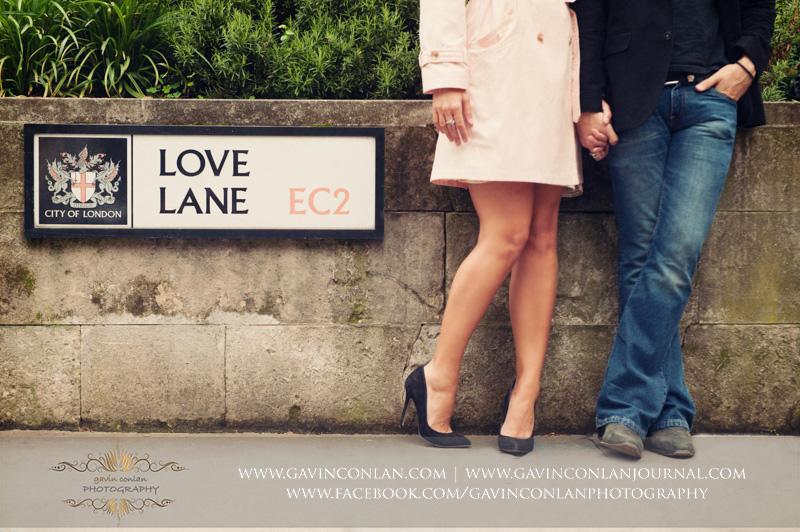 creative portrait of the couple standing on Love Lane EC2. London engagement photography by gavin conlan photography Ltd