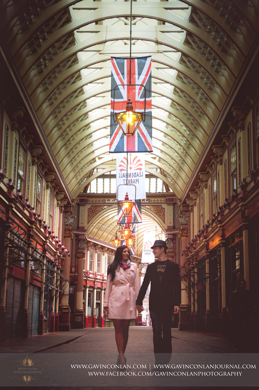 couple holding hands walking through Leadenhall Market. London engagement photography by  gavin conlan photography Ltd