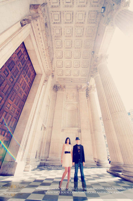 full length fashion portrait of the couple holding hands at St Pauls Cathedral. London engagement photography by  gavin conlan photography Ltd