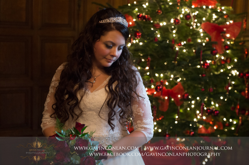 stunning emotive portrait of the bride standing in front of the Christmas tree.Wedding photography at Hengrave Hall by gavin conlan photography Ltd