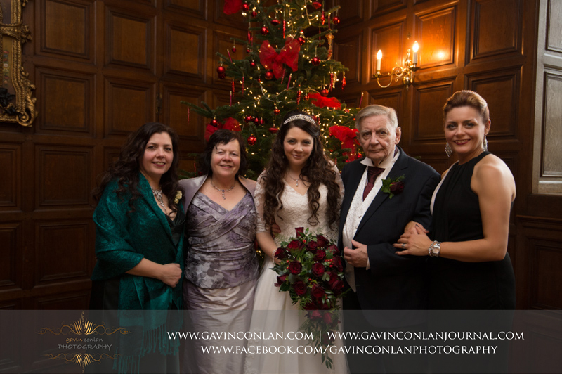 a portrait of the bride withher parents and her sisters in front of the Christmas tree.Wedding photography at Hengrave Hall by gavin conlan photography Ltd