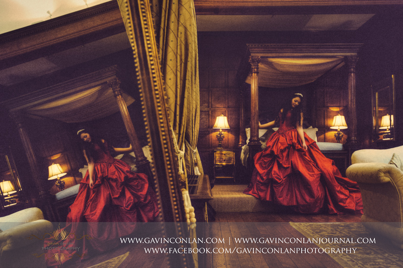 creative bridal portrait with the use of reflections in her red wedding posing in the bridal suite.Wedding photography at Hengrave Hall by gavin conlan photography Ltd