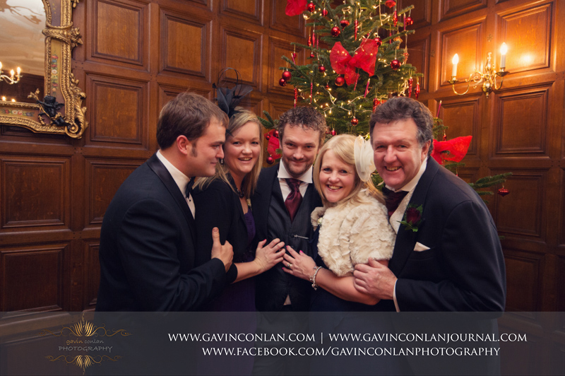 creative and emotive portrait of the groom withhisparents, his sister and brother in lawin front of the Christmas tree.Wedding photography at Hengrave Hall by gavin conlan photography Ltd