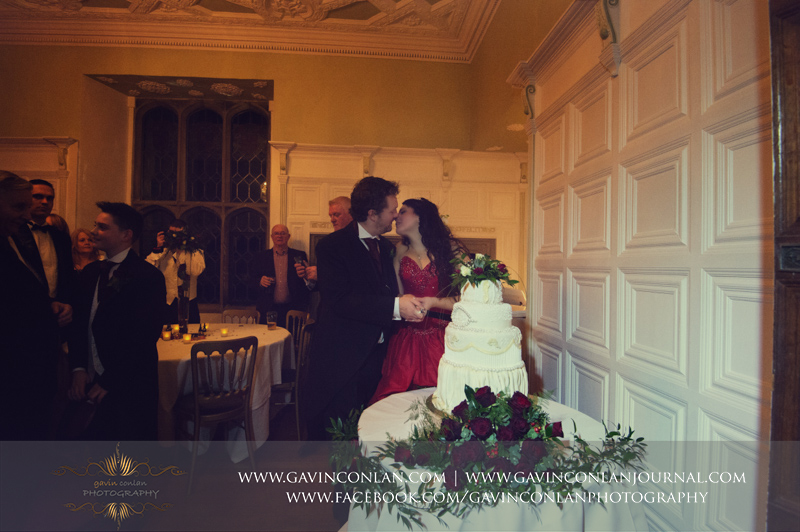 portrait of the bride and groom about to kiss each other during the cutting of their wedding cake.Wedding photography at Hengrave Hall by gavin conlan photography Ltd
