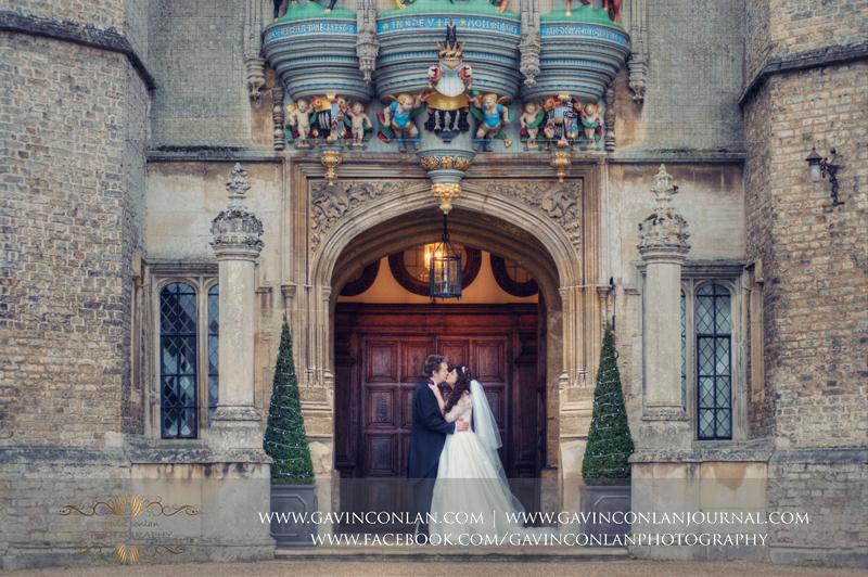 creative portrait of the groom and groom kissing outside the front of Hengrave Hall.Wedding photography at Hengrave Hall by gavin conlan photography Ltd