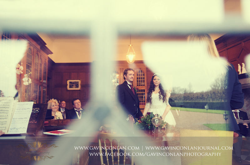 creative portrait of the bride and groom during their official wedding ceremony.Wedding photography at Hengrave Hall by gavin conlan photography Ltd