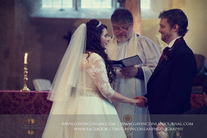 portrait of the groom holding his brides hand during the church service.Wedding photography at Hengrave Hall by gavin conlan photography Ltd