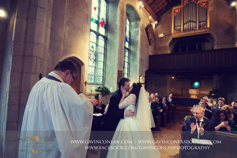 portrait of the bride and groom kissing at the end of their wedding ceremony. Wedding photography at Hengrave Hall by gavin conlan photography Ltd