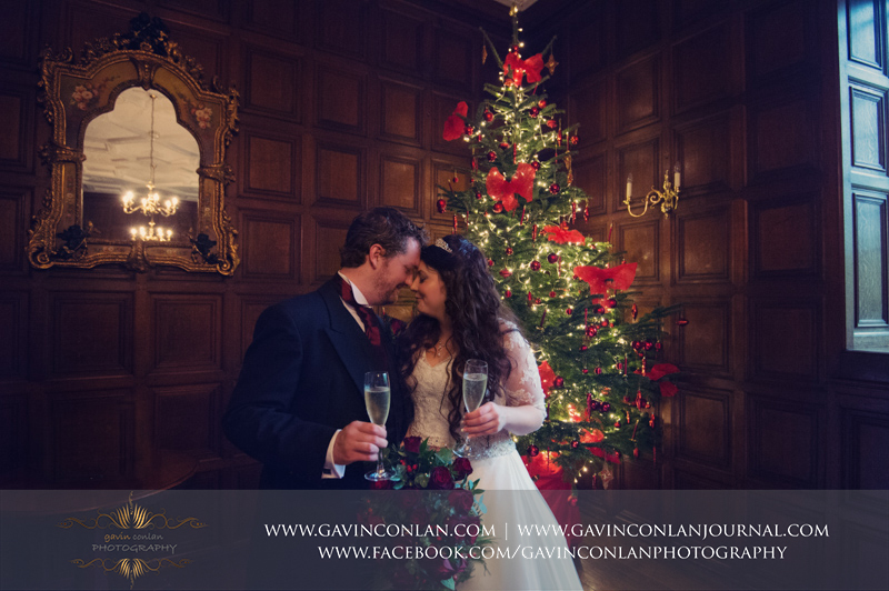 beautiful portrait of the bride and groom standing in front of the Christmas tree.Wedding photography at Hengrave Hall by gavin conlan photography Ltd