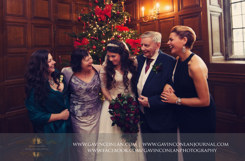 creative and emotive portrait of the bride withher parents and her sisters in front of the Christmas tree.Wedding photography at Hengrave Hall by gavin conlan photography Ltd