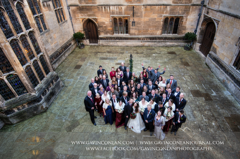 portrait of the all the guests in the courtyard in Hengrave Hall. Wedding photography at Hengrave Hall by gavin conlan photography Ltd