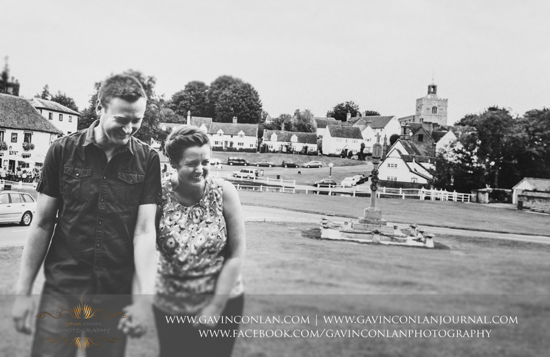 Couple holding hands and laughing in Finchingfield. Essex engagement photography by  gavin conlan photography Ltd