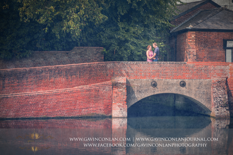 sarah and mark cuddling on bridge in Finchingfield. Essex engagement photography by  gavin conlan photography Ltd