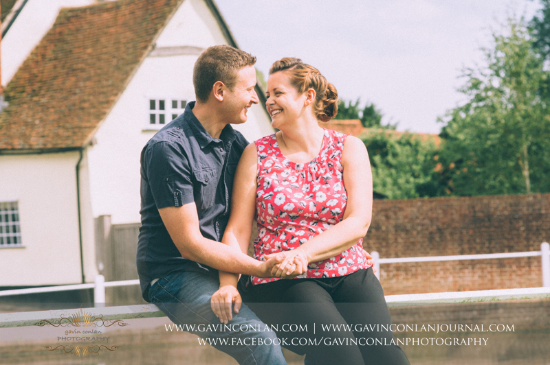 holding hands and laughing in Finchingfield.Essex engagement photography by gavin conlan photography Ltd