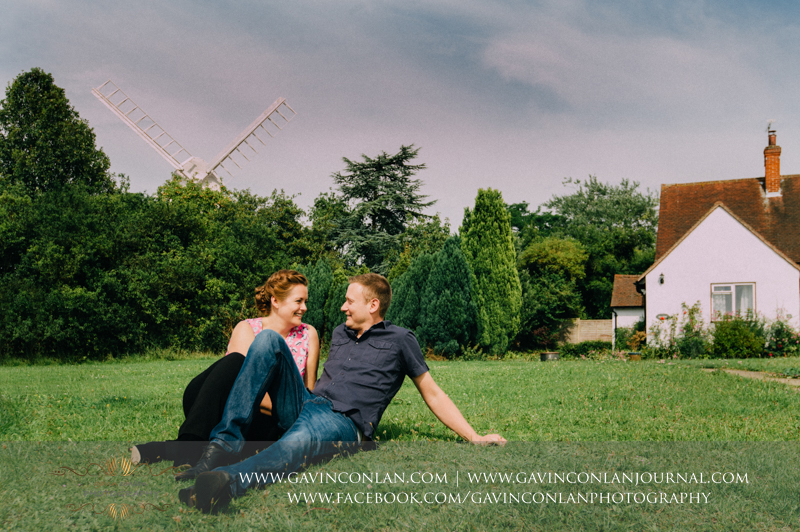 couple sitting on grass in Finchingfield.  Essex engagement photography by  gavin conlan photography Ltd