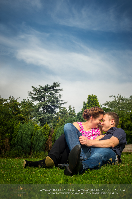 couple cuddling on grass in Finchingfield.  Essex engagement photography by  gavin conlan photography Ltd