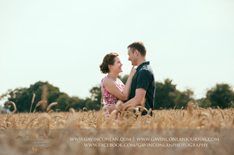 sarah and mark posing in corn field in Essex. Essex engagement photography by gavin conlan photography Ltd