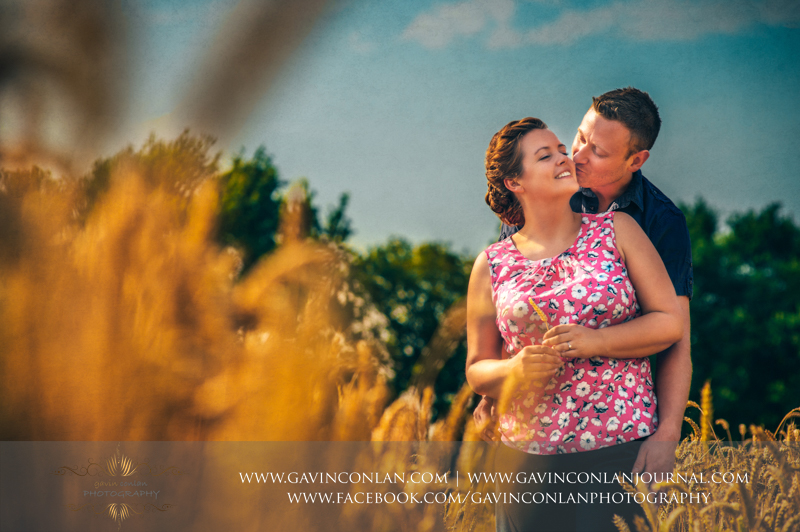 couple posing in a field in Essex.  Essex engagement photography by  gavin conlan photography Ltd