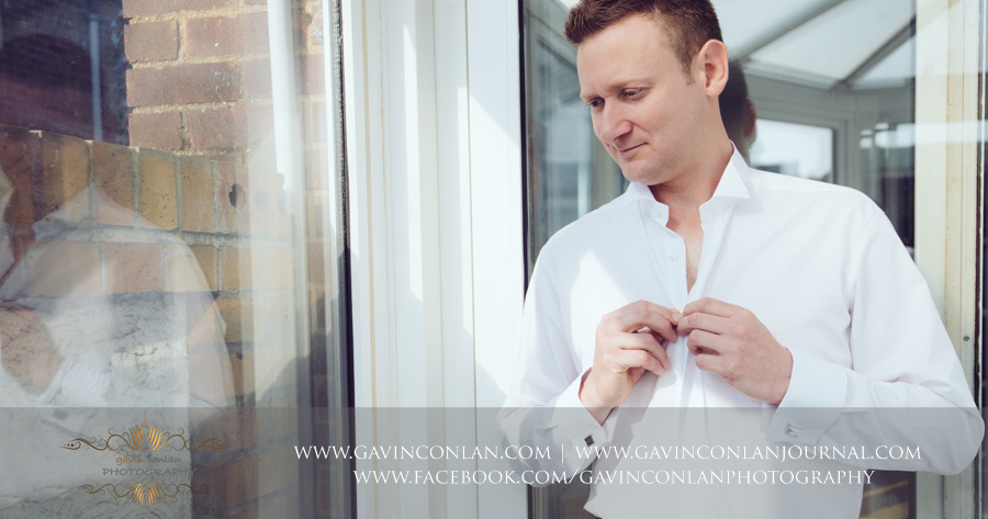 Groom getting dressed.Wedding photography by gavin conlan photography Ltd