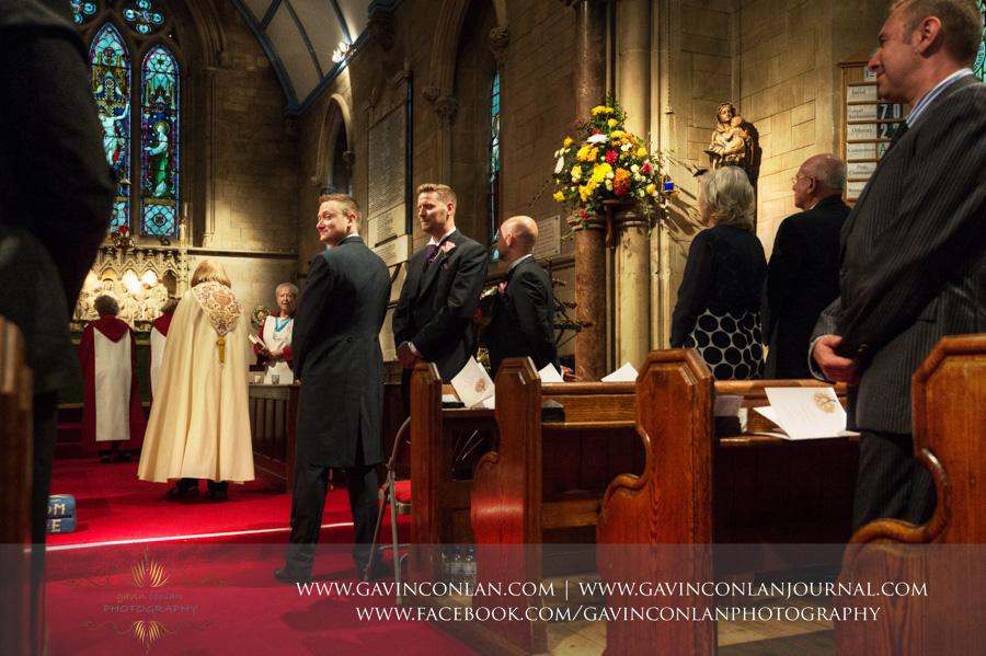 groom looking back at his bride walking down the aisle.Wedding photography at All Saints Cranham by gavin conlan photography Ltd