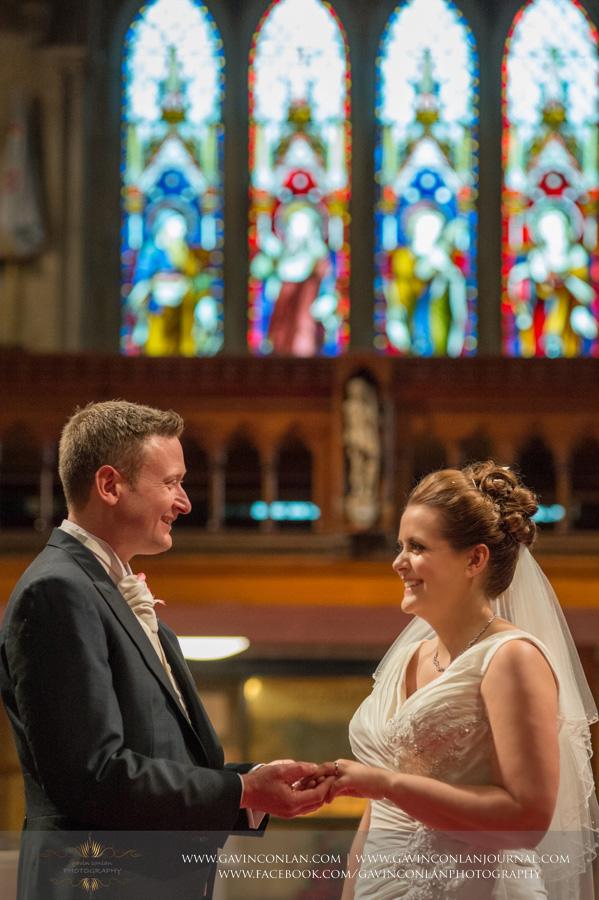 groom putting ring on brides finger. Wedding photography at All Saints Cranham by gavin conlan photography Ltd