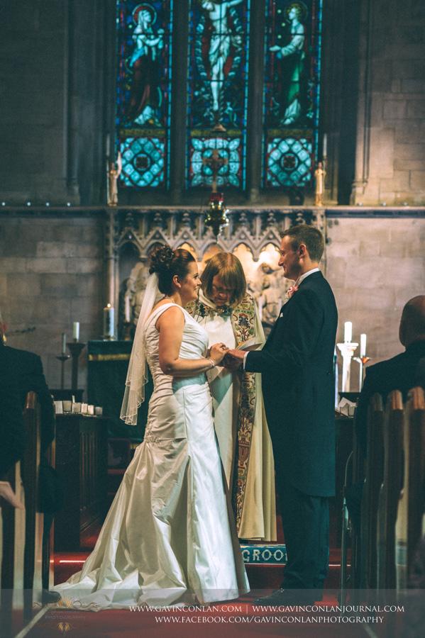 bride putting ring on grooms finger.Wedding photography at All Saints Cranham by gavin conlan photography Ltd