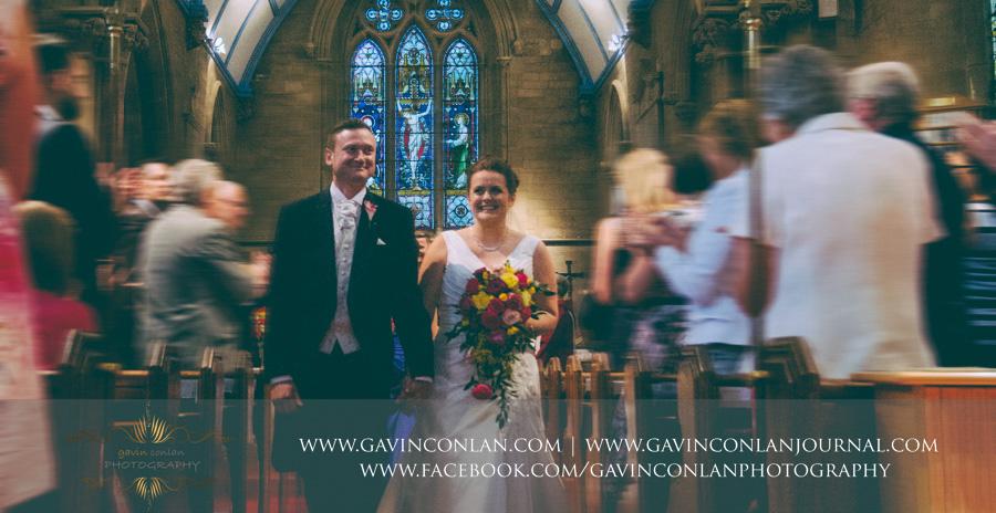 bride and groom walking down the aisle.Wedding photography at All Saints Cranham by gavin conlan photography Ltd