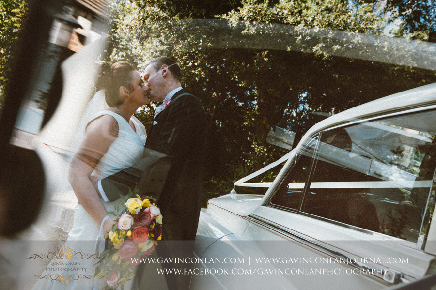 bride and groom kiss next to Rolls Royce bridal car.Wedding photography at  All Saints Cranham  by  gavin conlan photography Ltd