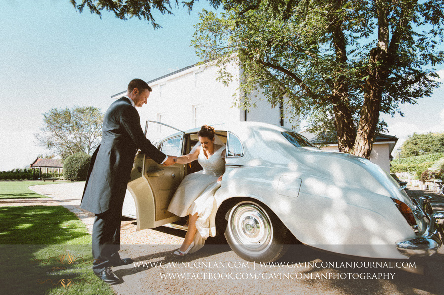 groom helping bride get out of Rolls Royce.Wedding photography at Moor Hall Venue by gavin conlan photography Ltd