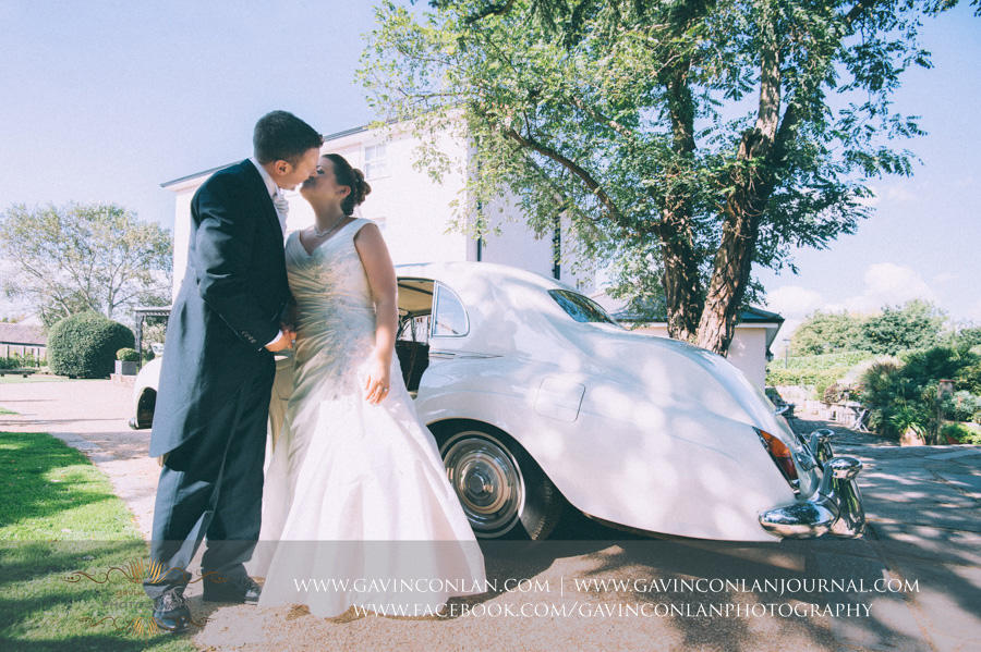 bride and groom kissing next to rolls royce.Wedding photography at Moor Hall Venue by gavin conlan photography Ltd