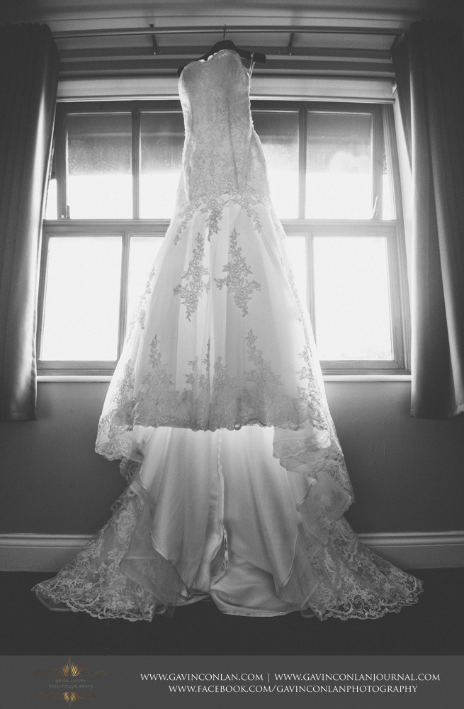 black and white detail photograph of the brides wedding dress hanging in the window. Wedding photography at  The Essex Golf and Country Club  by  gavin conlan photography Ltd