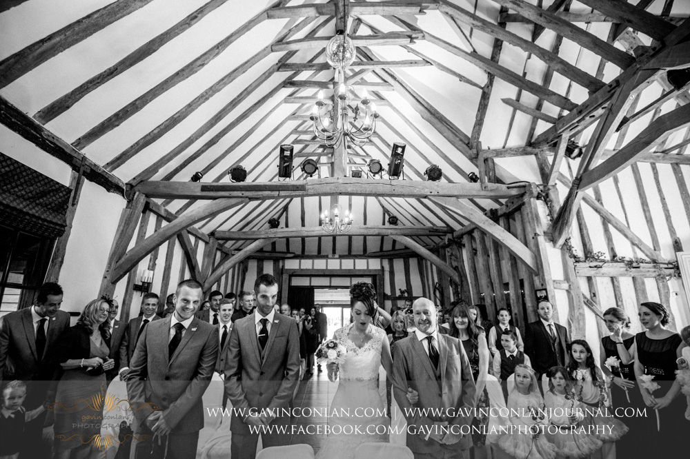 black and white portrait of the bride walking down the aisle with her father at the start of their ceremony. Wedding photography at  Crabbs Barn  by  gavin conlan photography Ltd