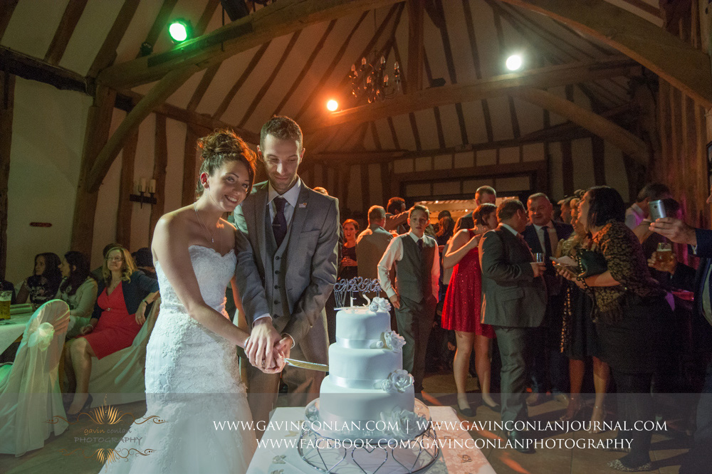 creative portrait of the bride and groom cutting their wedding cake with their family and friends looking on in the background. Wedding photography at  Crabbs Barn  by  gavin conlan photography Ltd