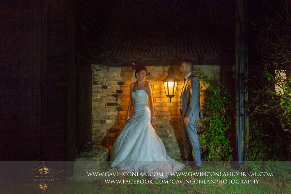 creative night time portrait of the bride looking back at her groom. Wedding photography at  Crabbs Barn  by  gavin conlan photography Ltd