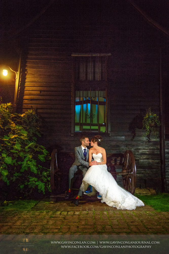 creative portrait of the bride and groom posing together outside of the barn on the wheeled seat. Wedding photography at  Crabbs Barn  by  gavin conlan photography Ltd