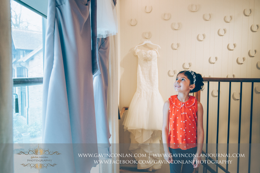 the brides niece looking up at her dress with a big smile on her face by  gavin conlan photography Ltd  taken at  Coworth Park Hotel