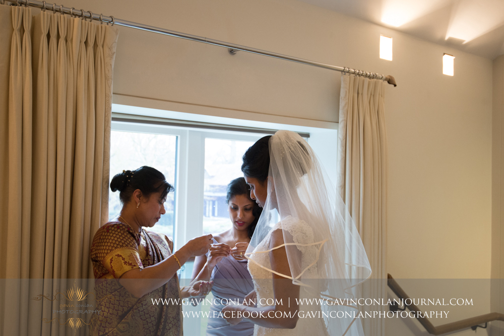 mother and sister of the bride helping the bride with her jewellery by  gavin conlan photography Ltd  at  Coworth Park Hotel