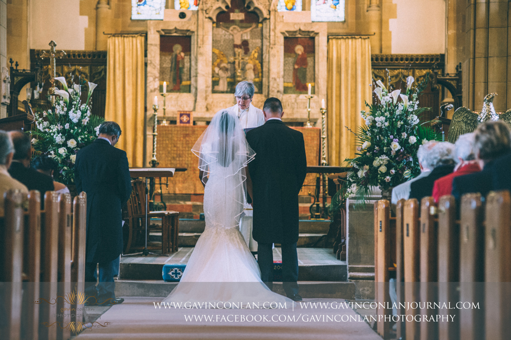 the bride and groom standing together as the ceremony begins, wedding photography at  All Saints Church Marlow  by  gavin conlan photography Ltd