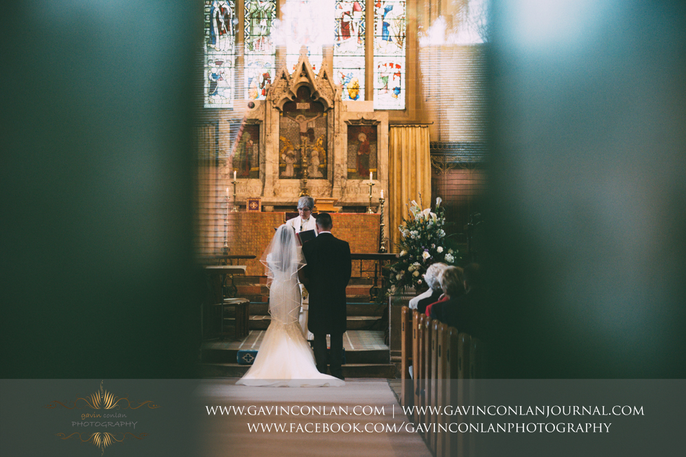creative ceremony shot of the bride and groom, wedding photography at  All Saints Church Marlow  by  gavin conlan photography Ltd