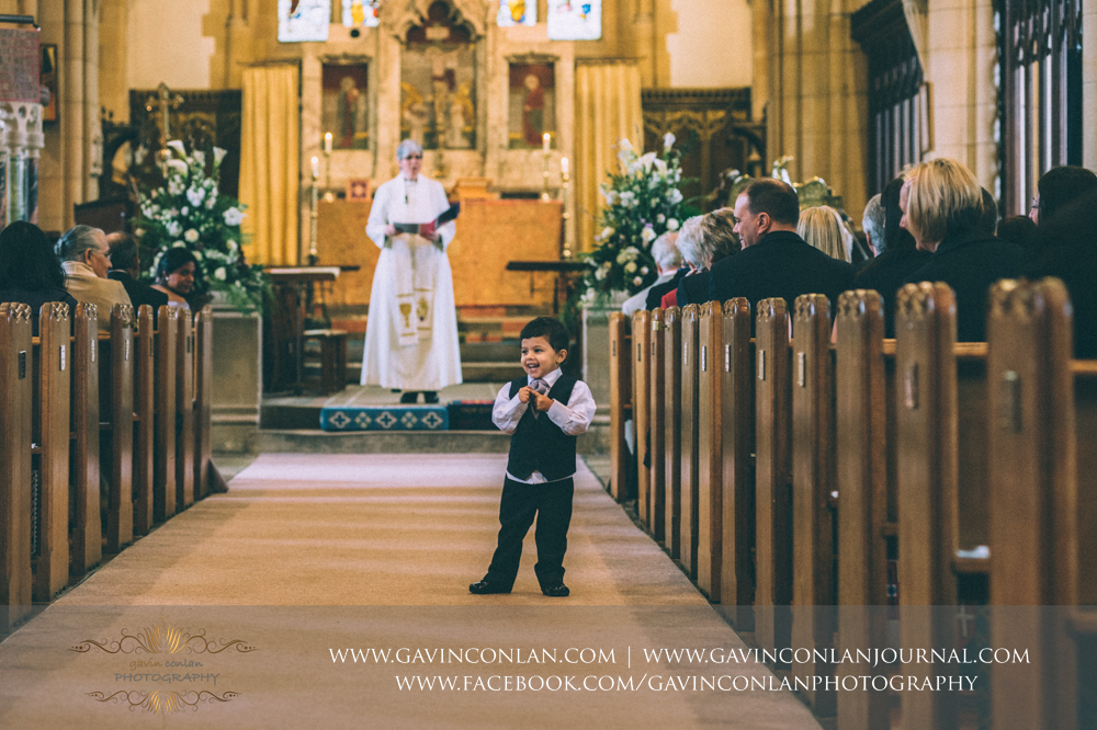 the perfect moment of a little boy standing in the aisle smiling during the ceremony, wedding photography at  All Saints Church Marlow  by  gavin conlan photography Ltd