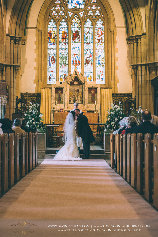 bride and groom sharing their first kiss as a married couple, wedding photography at  All Saints Church Marlow  by  gavin conlan photography Ltd