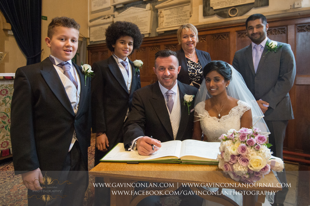 bride and groom with their witnesses signing their wedding register, wedding photography at  All Saints Church Marlow  by  gavin conlan photography Ltd