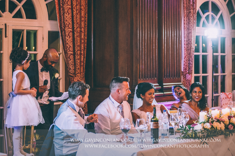 the brother of the bride giving his speech with the bridal party laughing, wedding photography at  Heatherden Hall Pinewood Studios  by  gavin conlan photography Ltd