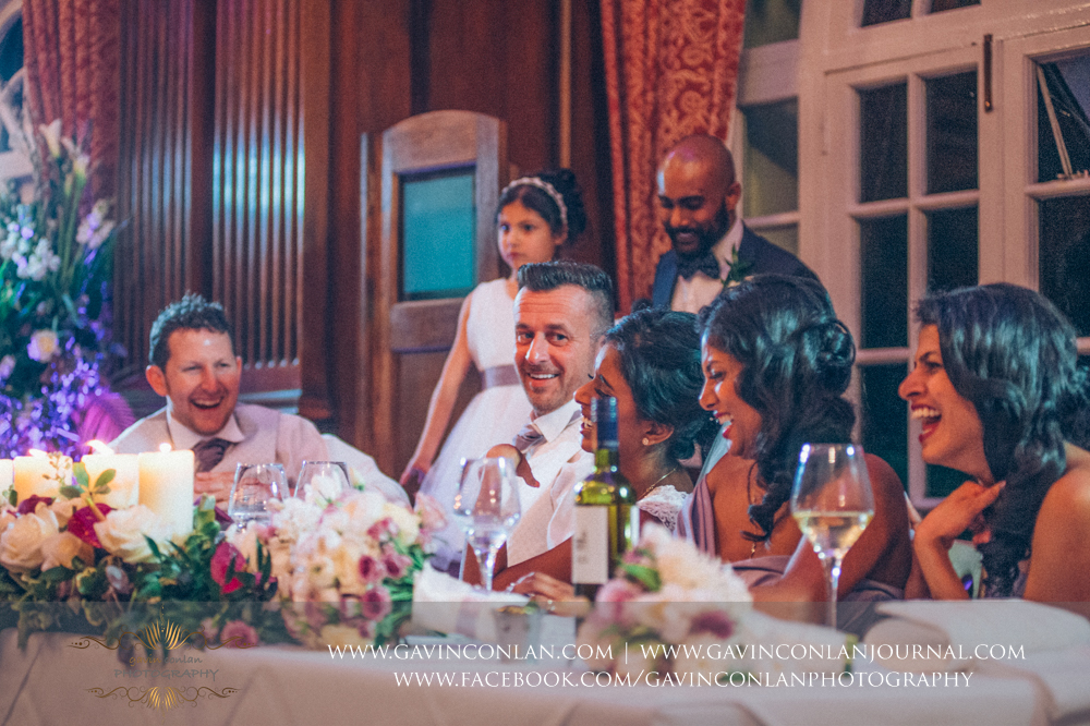 the bridal party laughing during the brother of the bride speech, wedding photography at  Heatherden Hall Pinewood Studios  by  gavin conlan photography Ltd
