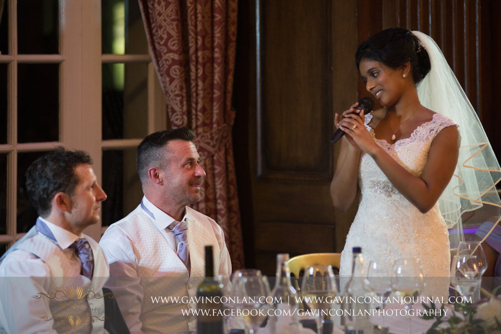 the bride giving her husband a heart felt message during her speech, wedding photography at  Heatherden Hall Pinewood Studios  by  gavin conlan photography Ltd