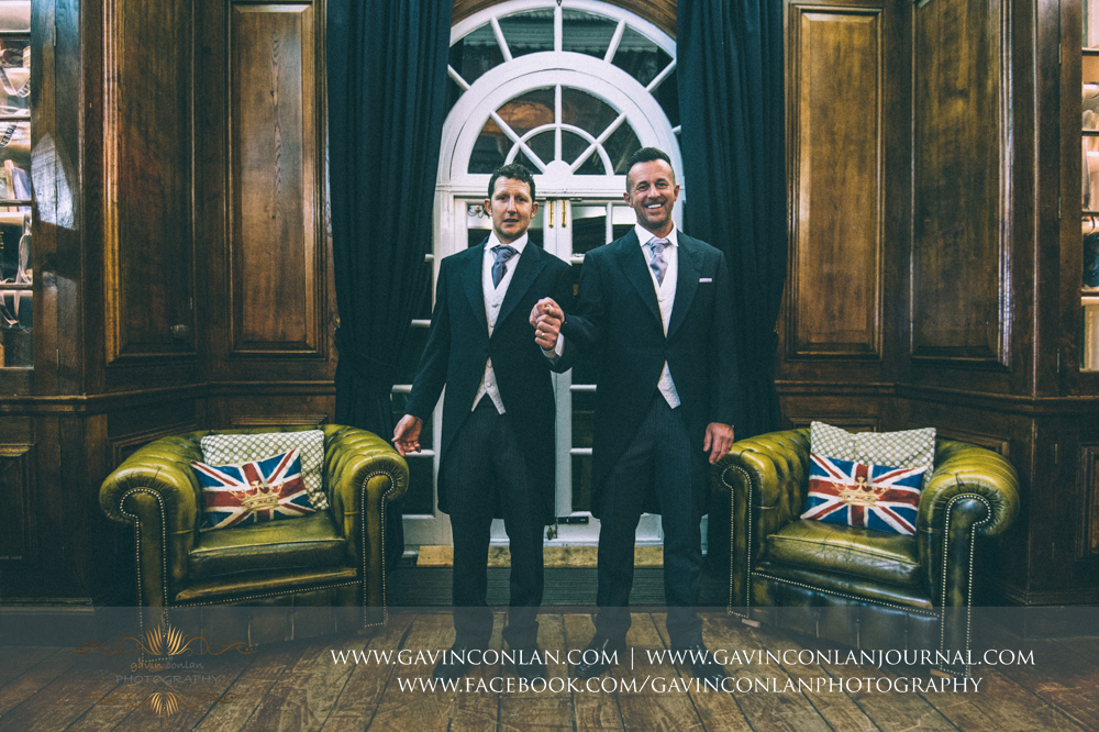 fun shot of the groom and his best man holding hands, wedding photography at  Heatherden Hall Pinewood Studios  by  gavin conlan photography Ltd
