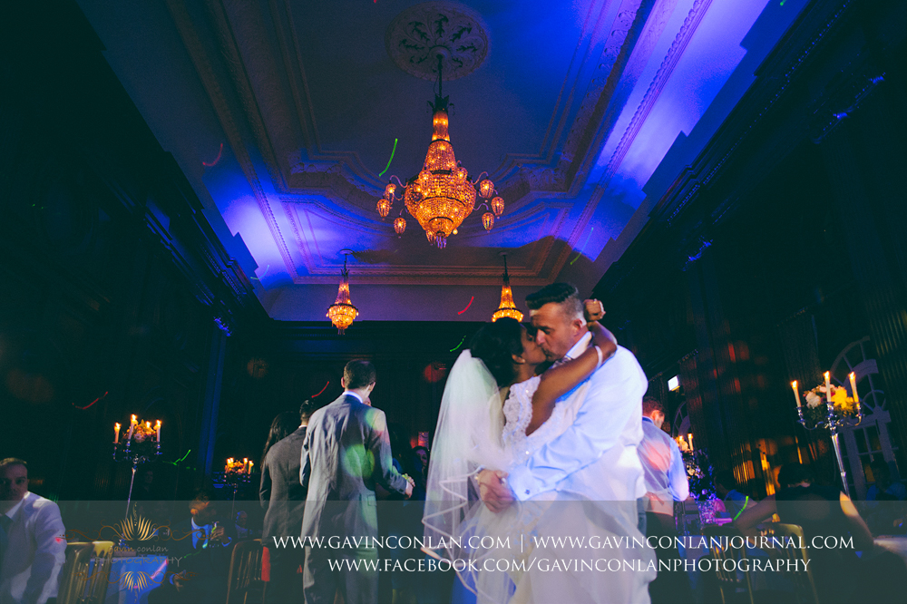 the bride and groom having a kiss during their first dance in the stunning ballroom, wedding photography at  Heatherden Hall Pinewood Studios  by  gavin conlan photography Ltd
