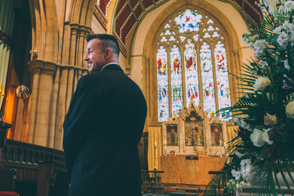 the groom looking back in happiness of seeing his bride walking down the aisle by  gavin conlan photography Ltd  taken at  All Saints Church in Marlow